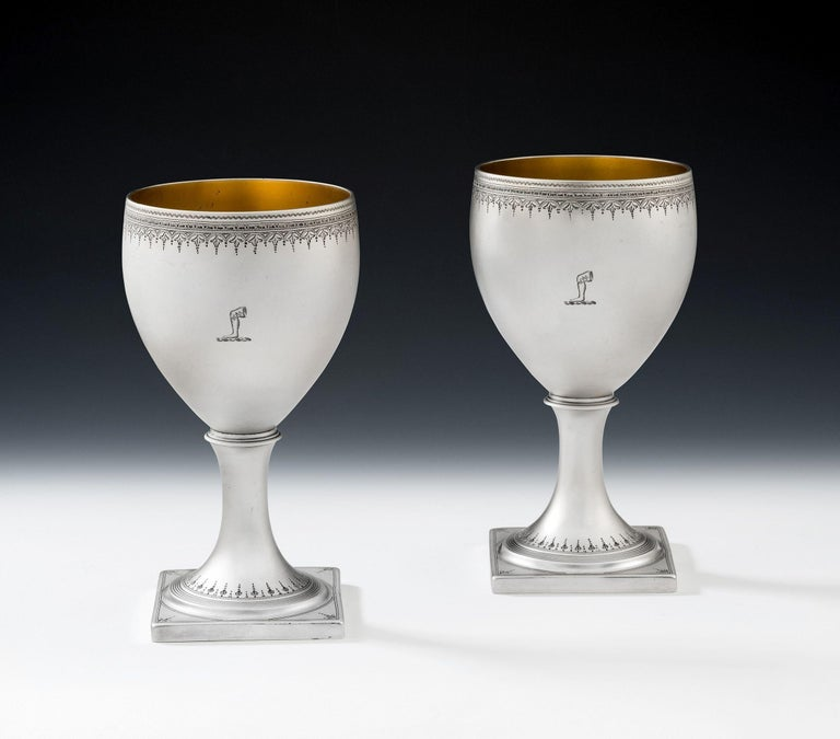 These exceptional Wine Goblets stand on a square pedestal foot decorated with circular reeding and an eclectic mix of bright cut and prick dot designs. The foot rises to a vase shaped bowl, with beautiful rim engraved with bright cut designs,