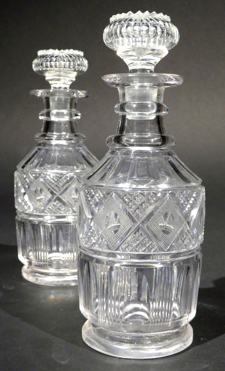 Both decanters of mallet form with panel-faceted shoulders and bodies, rising to triple-ringed necks fitted with their original dedicated and hexagonal shaped stoppers, the undersides of each base engraved with radiating star-cut motifs. Both in