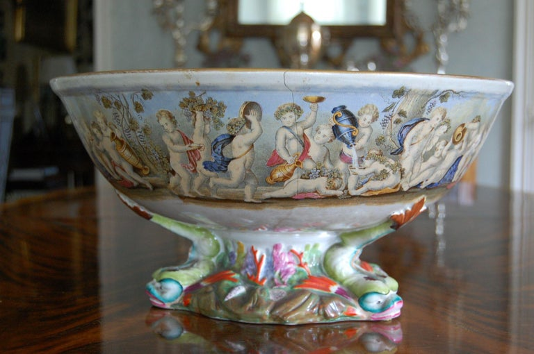 The transfer decorated pottery bowl with its interior decorated with five drunken Bacchic putti beneath a frieze of other frolicking and drunken Bacchic putti, the similarly decorated exterior raised on an elaborate sea life base moulded with three