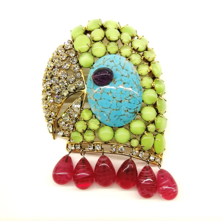 A striking and well known design from Iradj Moini, of a parrot's head, hand made and all stones hand set in 18 carat plated brass. A beautiful combination of colours , as always with this designer - mint green, turquoise, amethyst and ruby, with