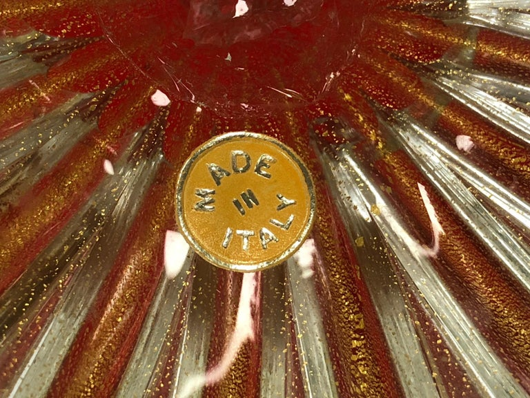 The lobed bowl of vivid fire-engine red raised on a clear foot, all with gold metal inclusions (aventurine), with original foil label.