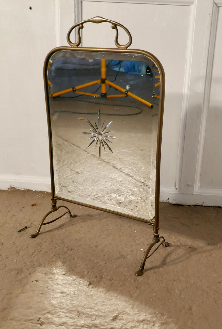 A Victorian Art Nouveau brass and sunburst mirror fire screen