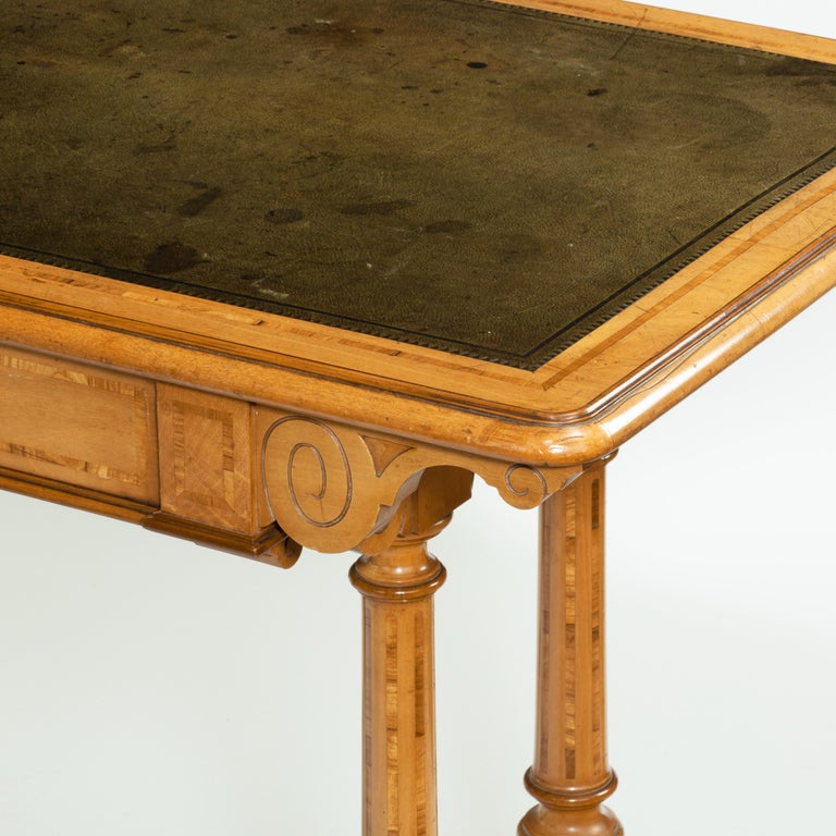 A Victorian birch or satinwood writing table, attributed to Holland and Sons, the leather-inset top with moulded edges above a disguised single frieze drawer, the end supports comprising twin turned columns set on splayed square section legs joined