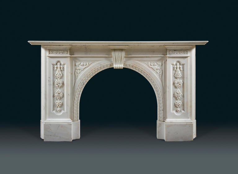 A late Victorian Carrara marble fireplace with arched moulded opening, headed by a corbel keystone flanked by foliate spandrels. The heavy jambs inset with arched lozenges carved with posies of flowers suspended from ribbons. The whole supported on