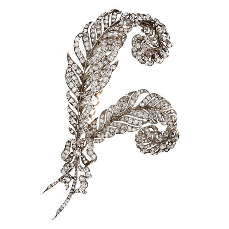 A Victorian diamond-set feather brooch, the two realistically carved feathers encrusted with old European-cut diamonds, tied with an old-cut diamond-set ribbon, the diamonds weighing approximately a total of 20 carats, all set in silver to yellow