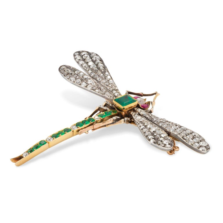An antique Russian emerald and diamond dragonfly brooch, the body a square-cut emerald with estimated weight 0.6 carats, the tail set with twelve emeralds and four diamonds, the wings and legs set with old-cut and rose-cut diamonds, the eyes a pair