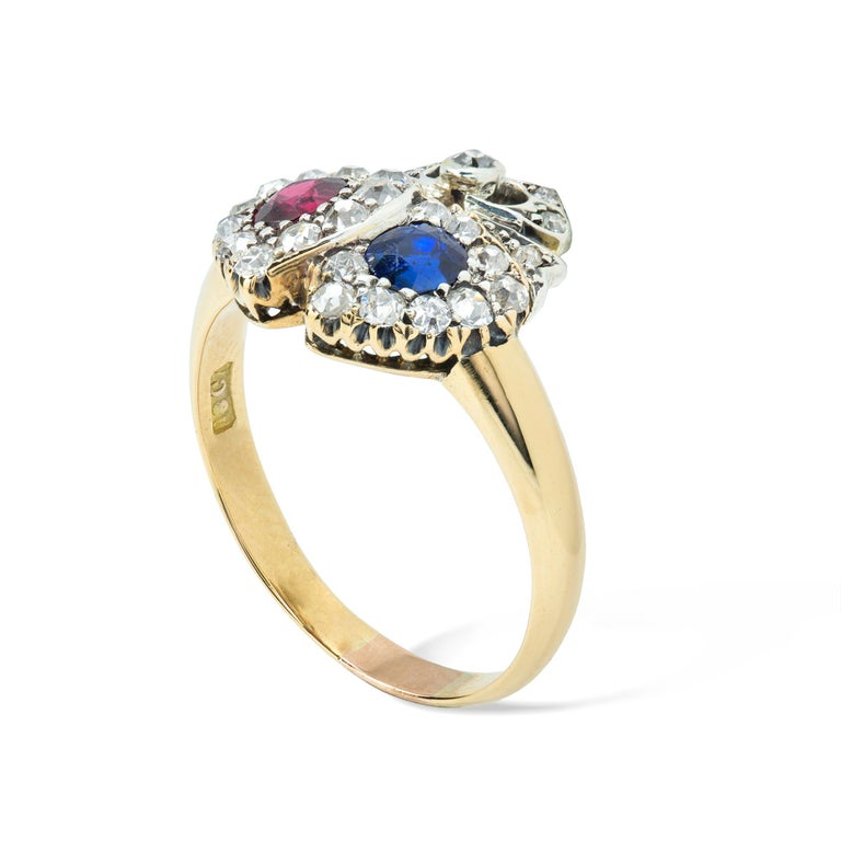 A Victorian ruby, sapphire and diamond double heart ring, set with a round-shaped ruby weighing approximately 0.30 carats and a round-shaped sapphire weighing approximately 0.20 carats, both set to the centre of an old brilliant-cut diamond cluster