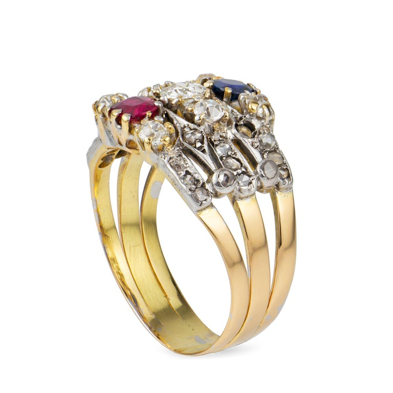 A Victorian ruby, sapphire and diamond harem ring, consisting of three bands, the one centrally-set with a ruby, the second with an old-cut diamond and the third with a sapphire, each set between two small old-cut diamonds and rose-cut diamond