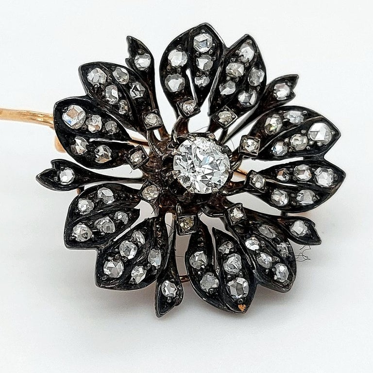 A Victorian Silver on Gold Diamond Flower Brooch from Circa 1860,   The pin of the brooch is 18kt gold, there is an option of taking the pin off and at the back of the jewel there are two hinges to be worn as a pendant when wanted.  Hallmarks :