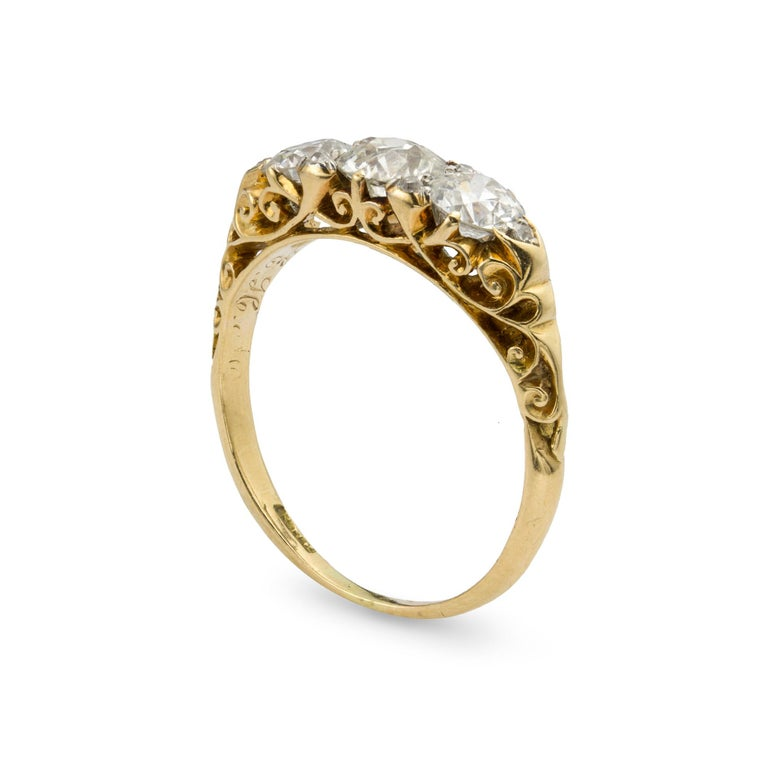 A Victorian three stone diamond ring, set with three old brilliant-cut diamonds, estimated total diamond weight 1.5 carats, set with rose-cut diamonds, all on an 18ct yellow gold carved mount, circa 1880, the head measuring 0.6x1.9 cm, gross weight