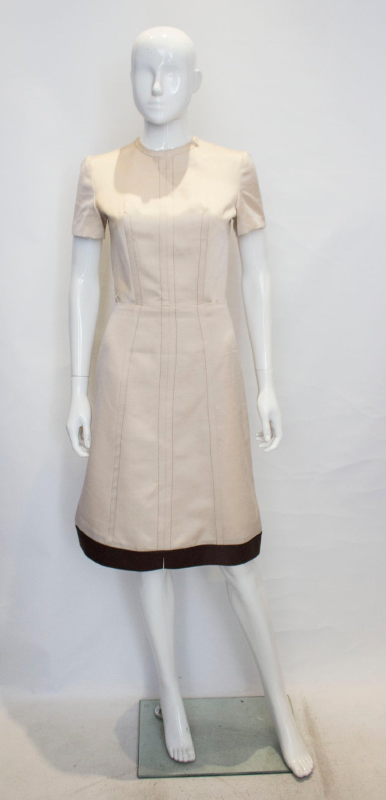 A vintage 1960s cream fitted raw silk dress with a brown silk hem   fitted at the waist zips up the back with a interesting stitch detail across the bodice  measurements taken flat in inches   bust - 16 waist - 13 length - 41