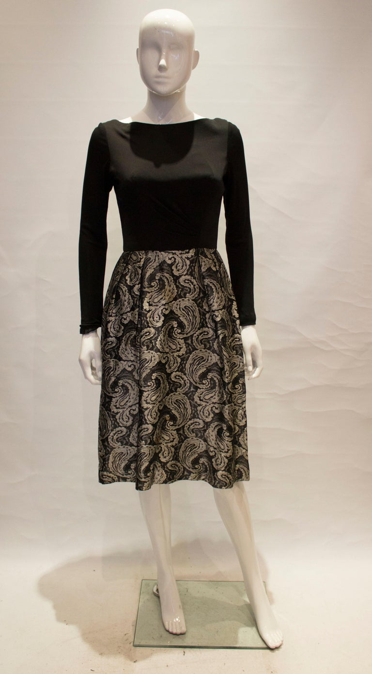 A lovely 1950s brocade dress with a black top and silver and black paisley printed skirt, it has a lovely low back and zips at the back   measurements taken flat in inches are  bust - 16inches waist - 13inches  length - 42inches