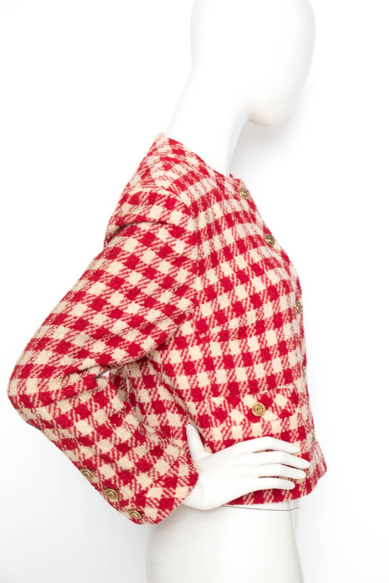 A 1980s classic Chanel red and white collar-less boucle blazer with a button-down front and two elegant patch pockets in front. The gold-toned Chanel buttons feature an intertwined moon and sun. The jacket is fully lined.   The size of the item