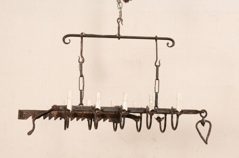 A vintage French ten-light forged-iron chandelier made from a 19th century spit-jack. This French hanging light-fixture, from the mid-20th century, has been fashioned from an earlier 19th century spit-jack, which was once used as a type of