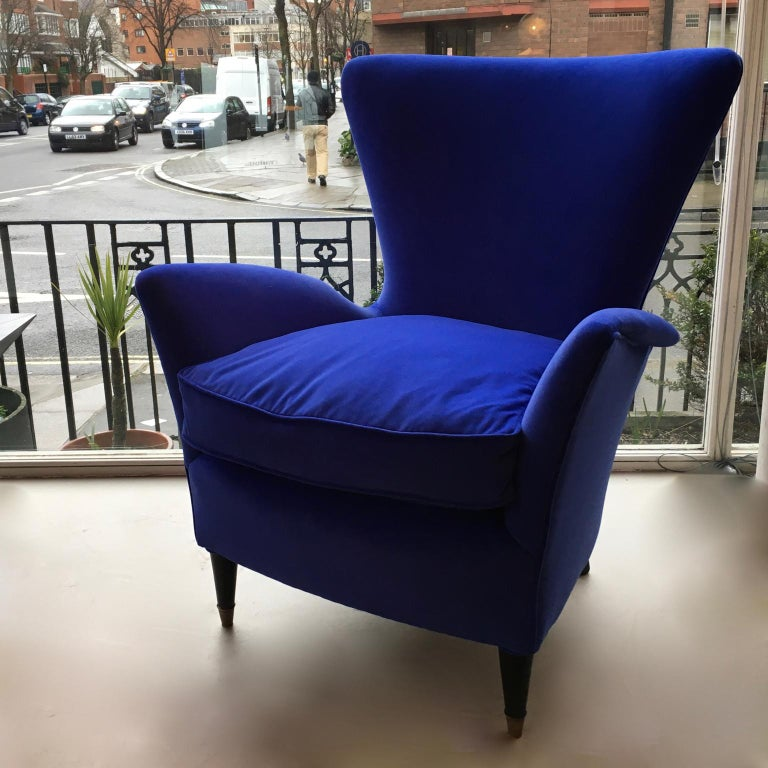 A smart, organic, comfortable and compact armchair, in a royal blue velvet, Italy, 1950s. Black ebonized wooden legs with brass sabots. This model is often attributed to Gio Ponti, hotel Bristol, Merano. 1 lounge chair still available.