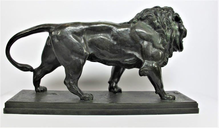 Bronze sculpture with a green patina representing a walking lion (on a rectangular base), his head is slightly turned towards the left, laid on a naturalist base. Old casting proof, signed BARYE on base, at the front right. Edited by founder