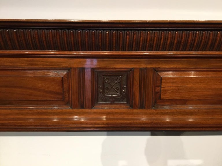 A walnut late Victorian period antique fire surround. The solid walnut top with a gadrooned and carved frieze above the central rectangular paneled section, having a finely carved coat of arms with a Latin inscription and cross keys motif. The