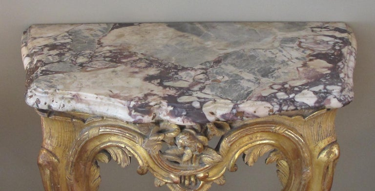 A curvaceous and well-carved Italian Rococo giltwood wall console table with calcutta viola marble top; with original thickly cut, serpentine-form marble top above a conforming console of finely carved floral bouquets and acanthus leaves.