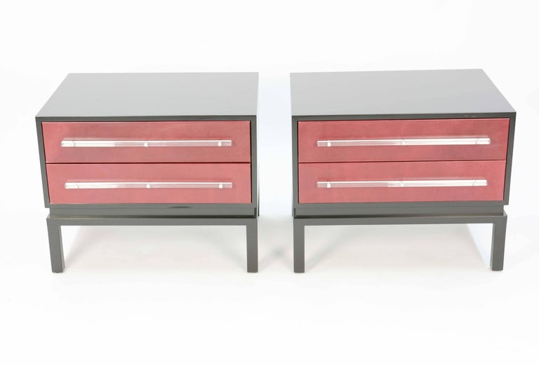 A wonderful and handsome pair of monumental nightstands after Paul Laszlo with leather fronts and Lucite pulls. The drawer have new glides and the Lucite and leather has been freshly recut and replace. The leather is blood wine in color and the