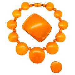 A wonderful orange Bakelite necklace, bangle and ring combination, 1930s