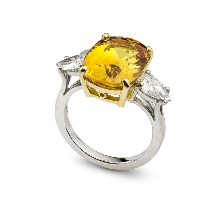A yellow sapphire and diamond ring, the cushion-cut sapphire accompanied by GCS report, stating the stone to be a natural sapphire  measuring 13.09 x 9.99 x 6.83mm and weighing 8.00 carats, four claw set in a yellow gold collet, flanked by two pear