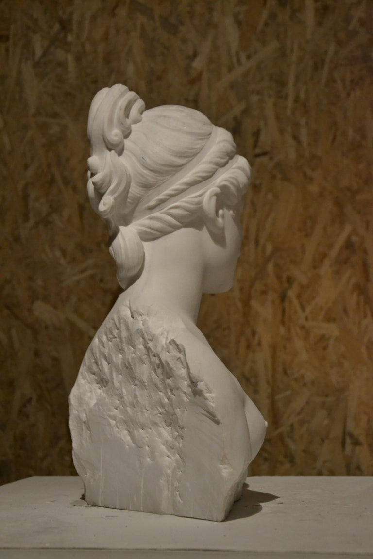 This gorgeous pure white Carrara marble bust depicts Venus. The Roman goddess of love, beauty, fertility and prosperity was sculpted by a young and talented Italian artist that lives and works in Pietrasanta near Carrara, Italy.  The sculptor