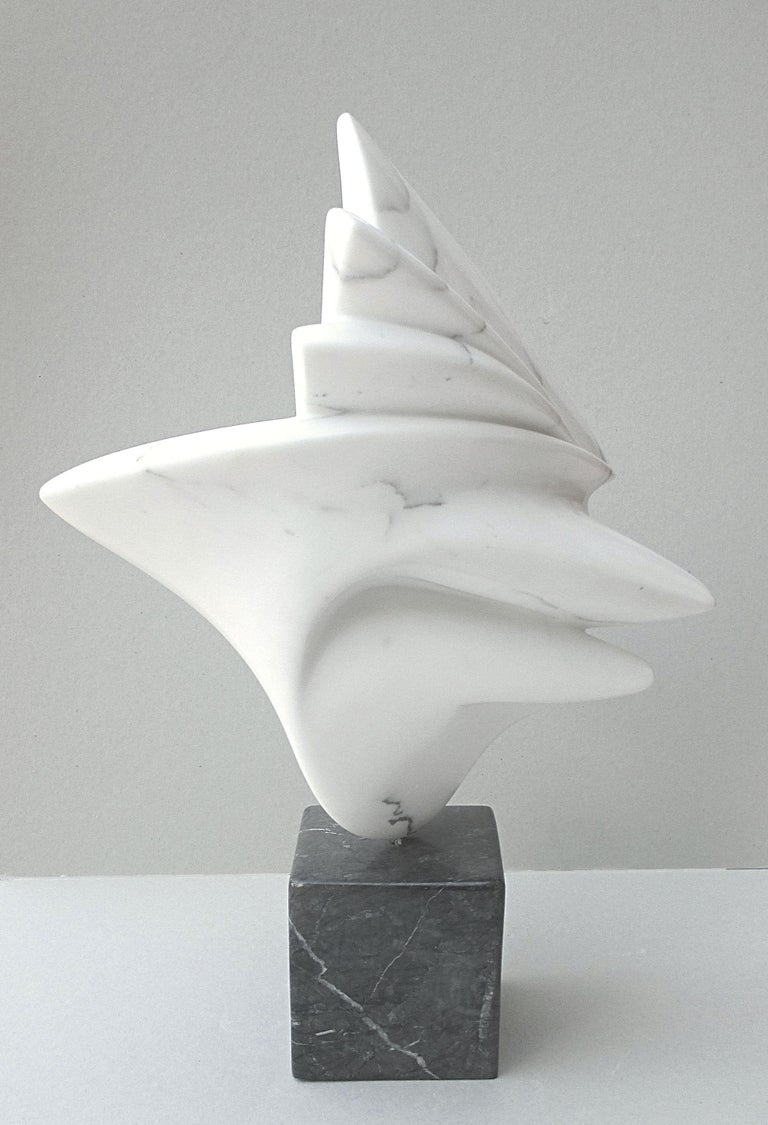This abstract sculpture in white Carrara marble has a very fine grain which provides a really soft touch.  The white marble body of the sculpture pivots on an axis connecting its large black veined marble base (base dimensions : 15 cm × 13.5 cm ×