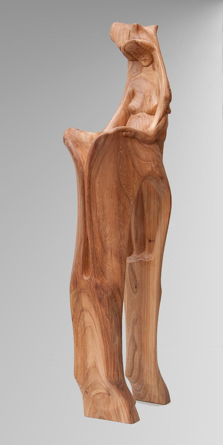 A very personal piece from this artist.  Human figures are carved in this horse sculpture, one of which is in the back of the horse neck and opens its back as a book.  The sculpture is in polished elm wood.  A graduate from the Academy of Fine Arts