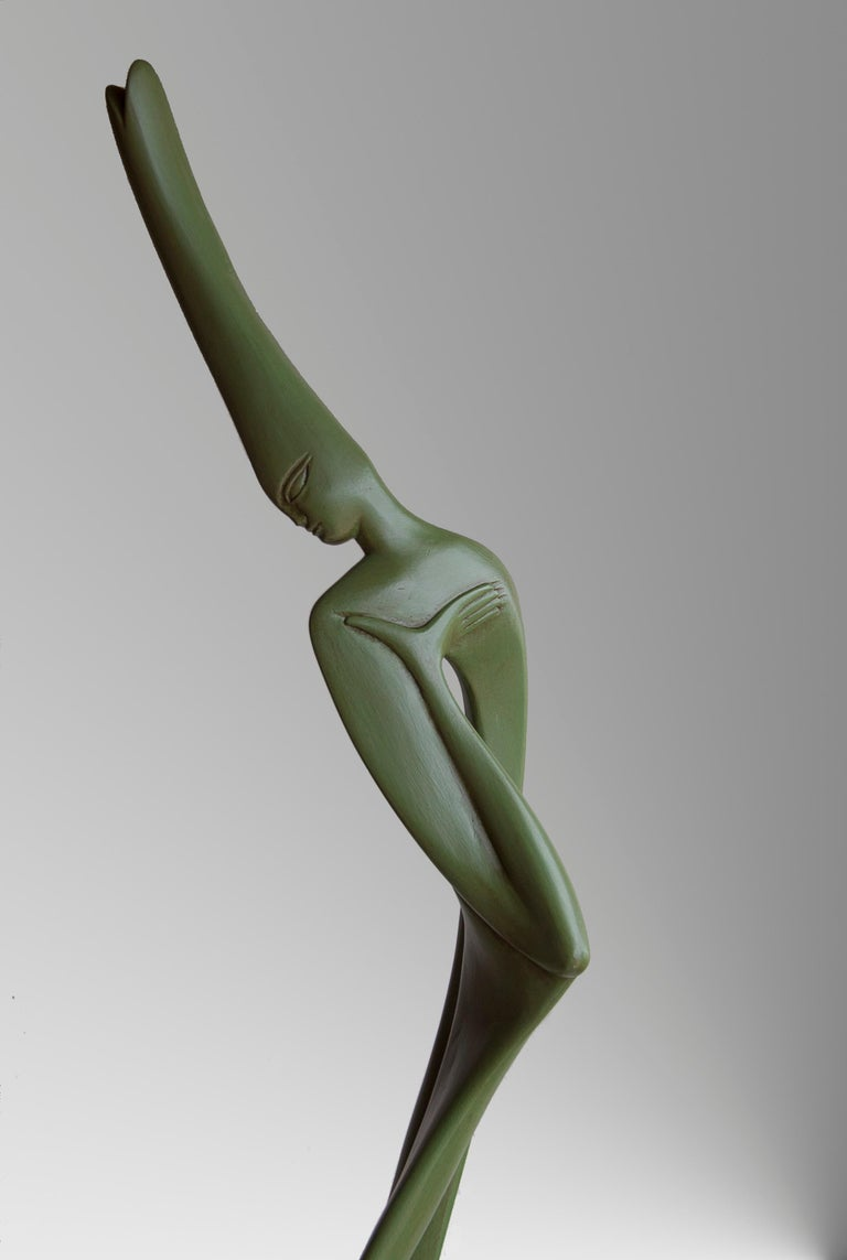 This feminine semi-abstract figurative sculpture depicts a slender woman in curves and softness, with an inner space.  The sculpture has an olive green patinated finish.  A graduate from the Academy of Fine Arts of Carrare, in Italy, Lutfi Romhein
