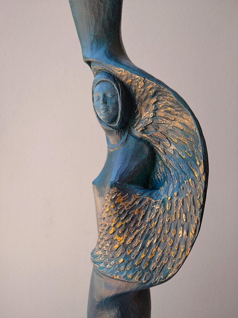 Peaceful face woman with bird, figurative oak wood sculpture covered with a blue and golden patina, by Lutfi Romhein.  A graduate from the Academy of Fine Arts of Carrare, in Italy, Lutfi Romhein is a sculptor of Syrian origin, leaving in France