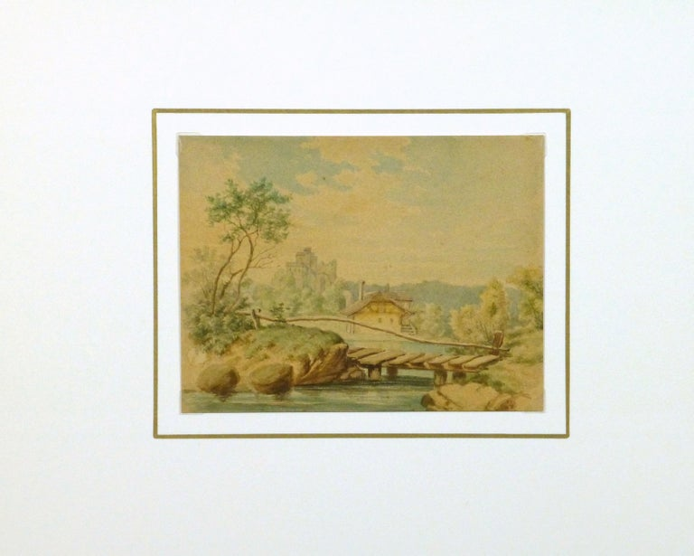 Watercolor painting of a tudor-style cottage overlooking a small lake with a footbridge and a grand castle in the background, circa 1890.   Displayed in a white mat with a gold border. Archival plastic sleeve and Certificate of Authenticity