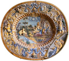 Oval Italian ceramic dish adorned with baroque figures and decoration in relief