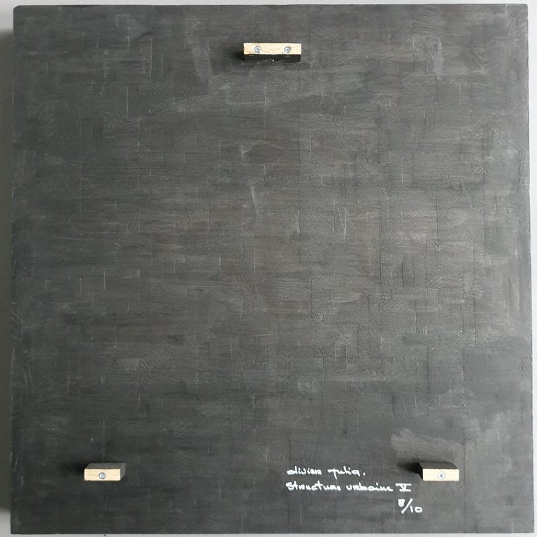 Structure urbaine V is a medium size contemporary modern sculpture painting relief by French-Dutch artist Olivier Julia. The relief is made from wood and finished with a mixture of anthracite grey and bronze acrylic paint . This art work hangs