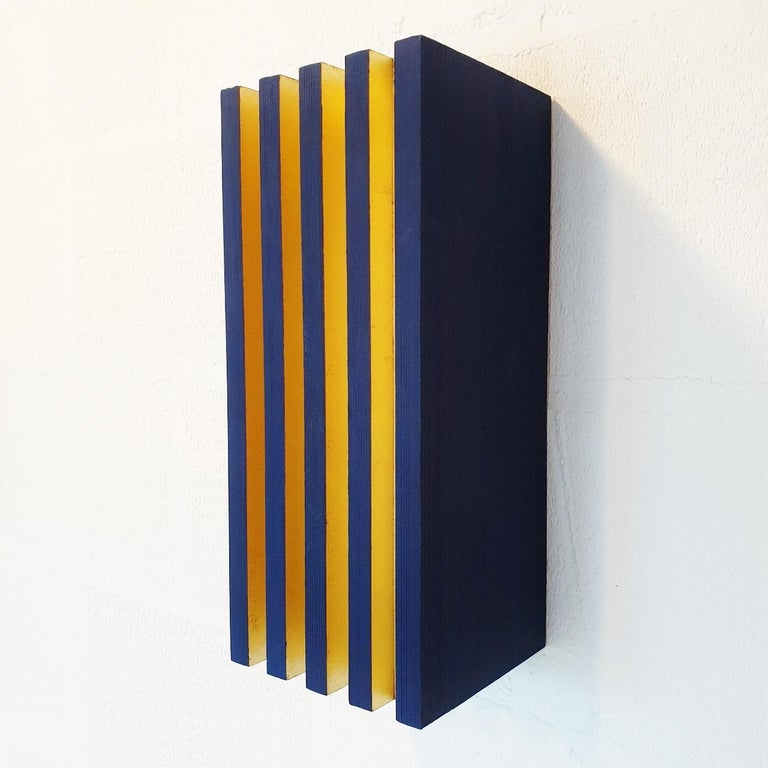 Luminosité verticale is a unique medium size contemporary modern sculpture painting relief by French-Dutch artist Olivier Julia. The relief is made from blue-painted textured wood with gold leaf and is part of his explorations of panel type