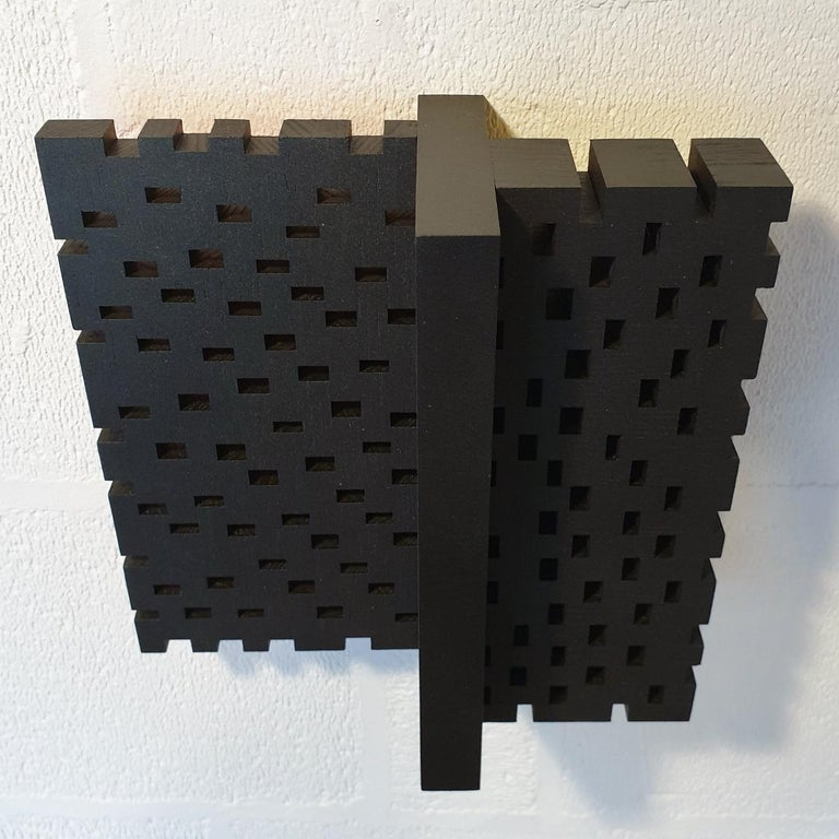 Superposition urbaine is a medium size contemporary modern sculpture painting relief by French-Dutch artist Olivier Julia. It is made from wood and mdf, with the front side finished with his well-known mixture of anthracite grey and bronze acrylic