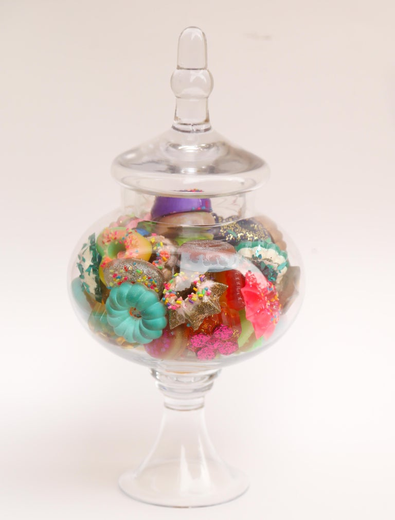 This is a glass candy jar filled with handmade resin donuts by Betsy Enzensberger. The donuts are loose and can be rearranged. The glass container can be emptied and cleaned as needed.  Although the artist is known for her melting popsicle