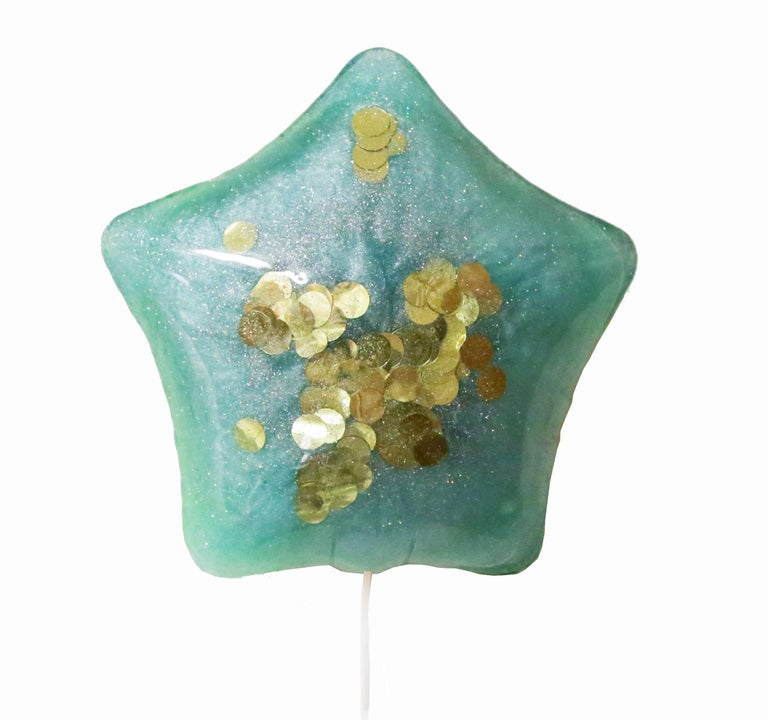 This is a solid resin wall sculpture by Los Angeles artist Betsy Enzensberger. It hangs with one screw, as if floating up the wall. This piece has a white, fabric string hanging from the bottom, but the artist recommends adding a shiny curled