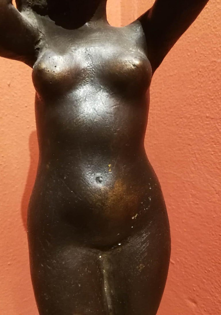 The small bronze statue portays a lady standing, with the arms lifted up while she's holding her long hair.  It can be dated to the 30-40 of the 20th century due to comparison with other similar works of the artist of the same period.  QuintoMartini
