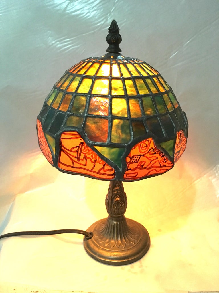 Handcrafted by TF Dutchman, Nike Deadstock is a one of a kind original Tiffany style stained glass lamp. Brilliant greens and yellows in a turtle back grid are enhanced by orange glass kiln fired sneaker motifs. Renderings of vintage Nikes add a