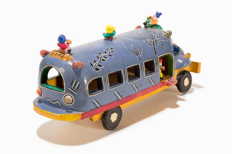 """""""Santa Cruz de las Huertas Jalisco"""" is a whimsical, charming and colorfully ceramic rendition  painted blue and red of a local bus that traversed the town where the artist Candelario Medrano lived. This bus was very important in the lives of the"""
