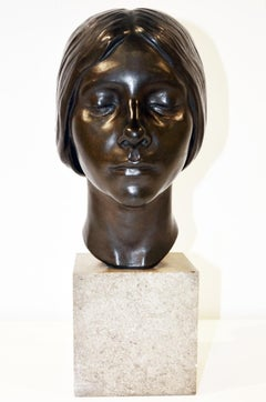 A bronze portrait bust of a young women