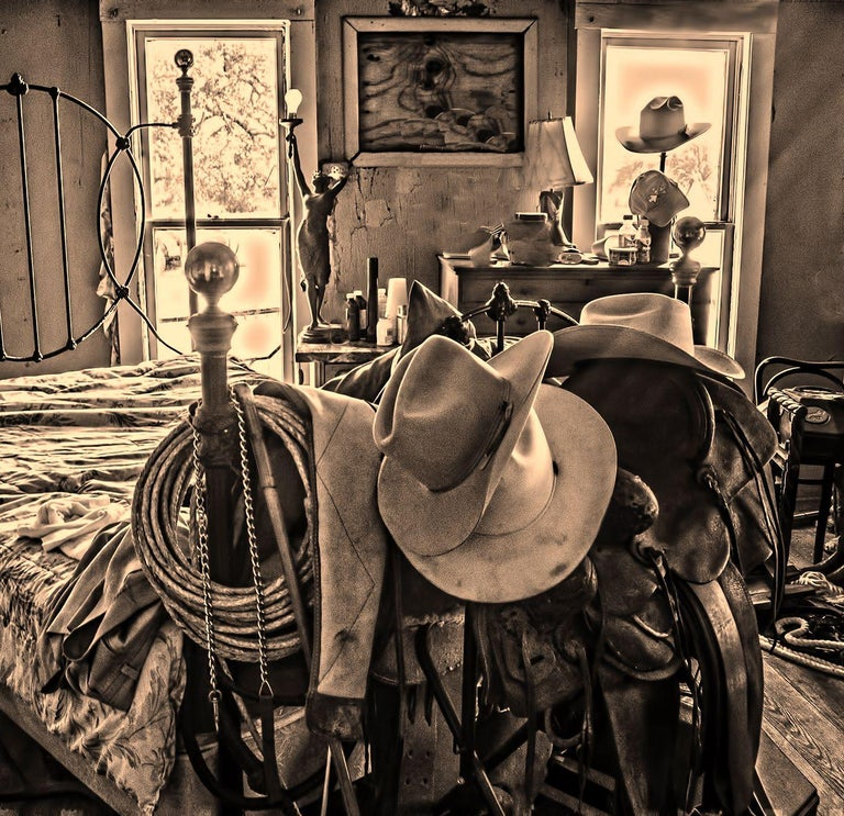 Bunkhouse - Sepia tone cowboy hats, saddle, & riding gear on bed frame, interior - Black Landscape Photograph by Mike Marvins