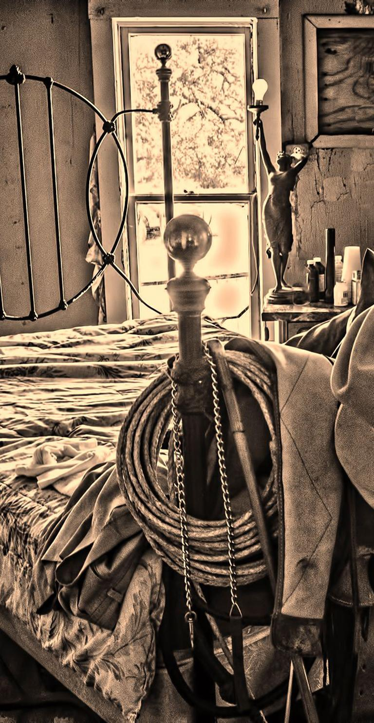 Bunkhouse - Sepia tone cowboy hats, saddle, & riding gear on bed frame, interior - Photograph by Mike Marvins