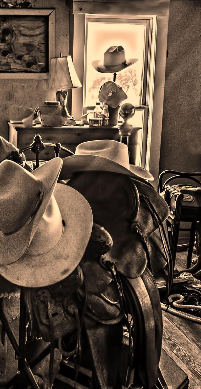 Bunkhouse - Sepia tone cowboy hats, saddle, & riding gear on bed frame, interior - Contemporary Photograph by Mike Marvins