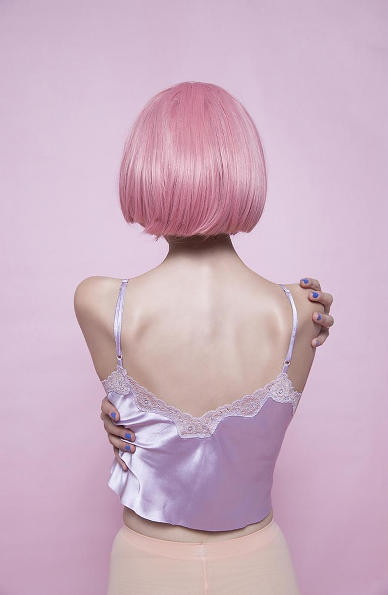 I am Her - Pop pink & purple self-portrait of woman from back, pink wig