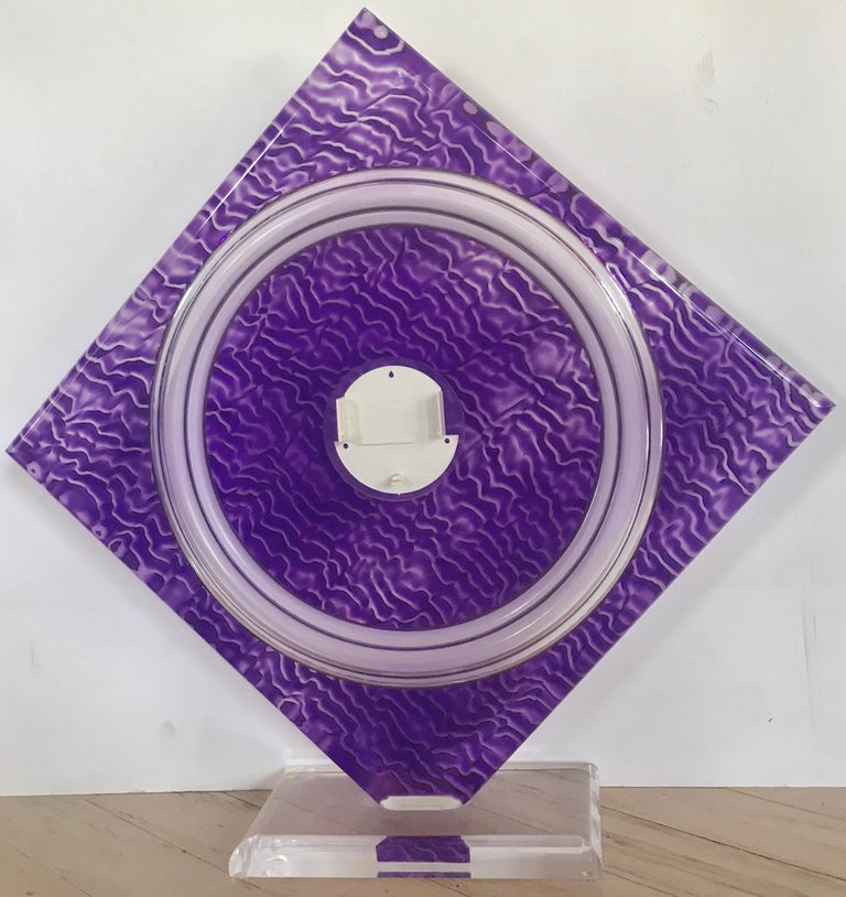 Norman Mercer (American, 1916-2007) Purple Cast Acrylic Sculpture. The amethyst diamond shaped sculpture is mounted on a beveled acrylic base. Cast with a repeating geometric pattern. In the back center of the step formed center circle, is a holder
