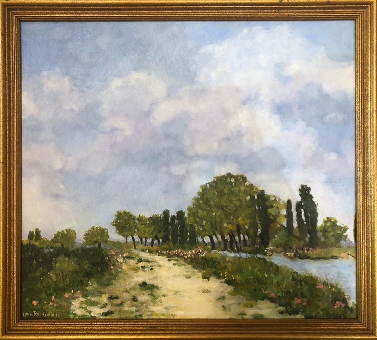 This landscape painting depicts a calm, serene water view with a predominant cumulus cloud-filled blue sky of summer. A green tree-lined beach lane with pink flowers is the central focus of the painting inviting the viewer to enter the sandy trail