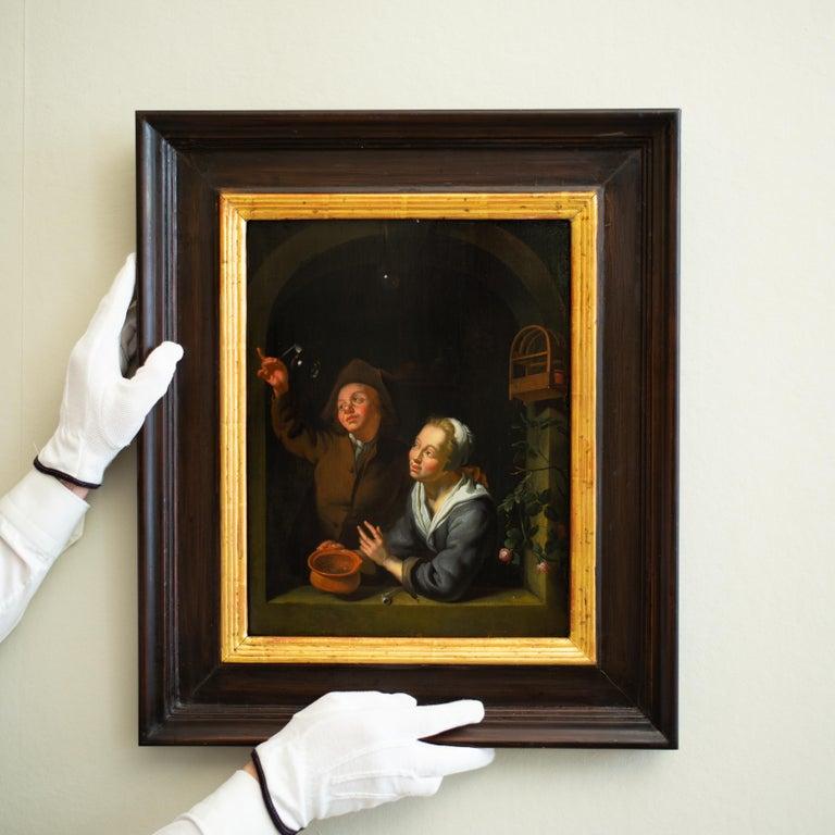 A Young Couple Blowing Bubbles at a Window, Follower of Louis de Moni, Oil Panel - Old Masters Painting by Louis de Moni
