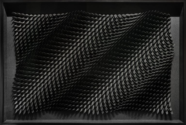 """This black abstract, geometric, wall-hanging sculpture titled """"Unholy 79"""" is an original artwork by Matthew Shlian made of black paper and iridescent black paper. Working at the forefront of technology and paper, the artist creates dimensional,"""