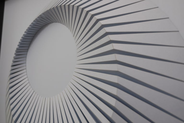 This beautiful geometric abstract wall sculpture is made out of colored laser cut paper that was hand folded by Yossi Ben Abu.